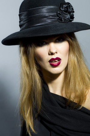 Young sexy woman in black retro hat with bright make up standing on grey background, vertical picture photo