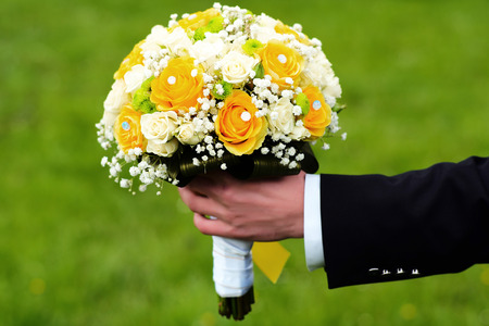 fiance: Fiance holding a bright wedding bouquet of white and yellow roses outdoor on green natural background, horizontal picture Stock Photo