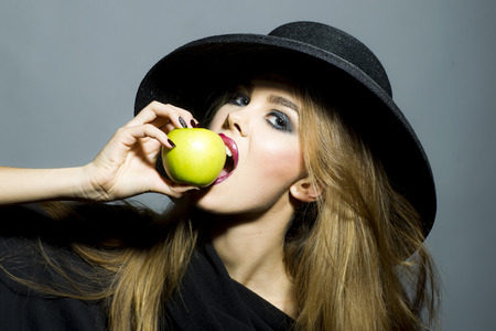 Beautiful young blonde sexy girl in retro black hat with bright make up biting fresh green apple standing on gray background copyspace, horizontal picture photo