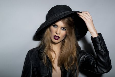perilous: Perilous seductive young blonde girl with bright make up in black leather jacket  and hat looking forward stanging on light grey background closeup copyspace, horizontal picture