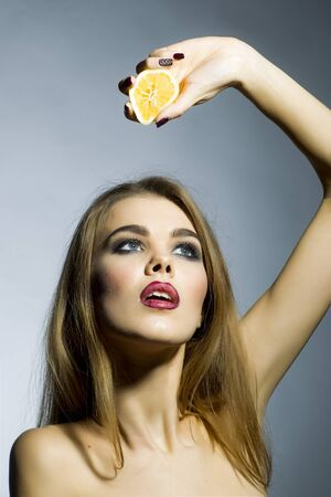 ardent: Ardent blonde young woman portrait with bright make up looking away holding half of fresh juicy orange standing on gray background copyspace, vertical picture