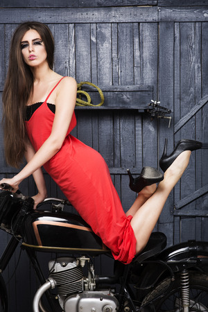 Sexual slim young girl with bright make up in long beautiful red dress looking forward sitting on old motorbike in garage on workshop background, vertical picture