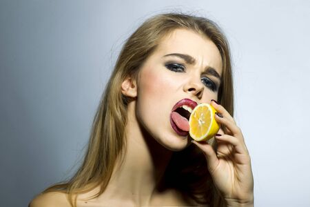Seducing blonde girl portrait with bright make up looking forward holding half of fresh juicy orange standing on gray background copyspace, horizontal picture photo