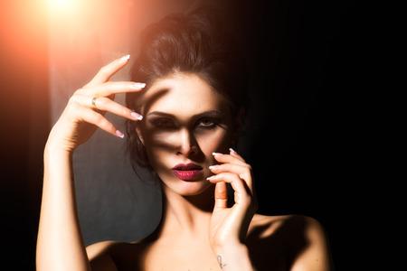 mujeres jovenes desnudas: Desnuda joven Morena posando sobre fondo oscuro Foto de archivo
