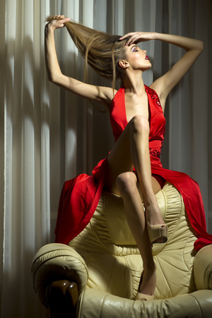 woman dress: Pretty young girl sitting on back of white leather armchair with closed eyes touching her hair in long red evening dress with big cut indoor on textile background, vertical picture