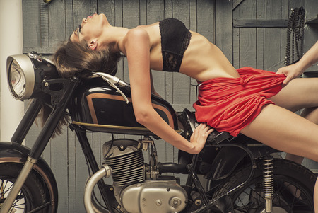 Slim sensual young girl with bright make up in flat red dress and black lingerie sitting on old motorbike in garage in sexy pose on workshop background, horizontal picture