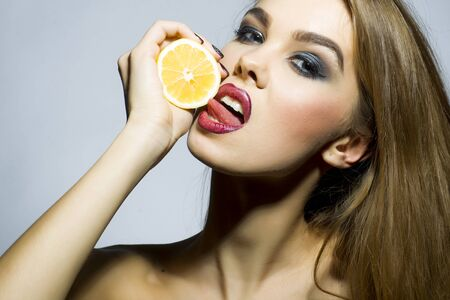 Sexual blonde girl portrait with bright make up looking forward holding half of fresh juicy orange standing on gray background copyspace, horizontal picture photo