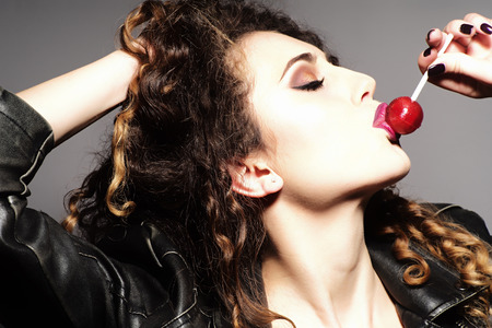 Attractive girl with curly hair and bright make up profile in leather jacket with long neck eating red sugar candy on grey wall background, vertical picture photo