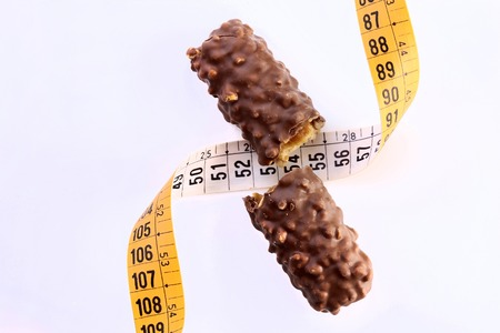 dietology: Appetizing chocolate bar broken in half with a measuring tape as a symbol of diet on white background, horizontal photo Stock Photo