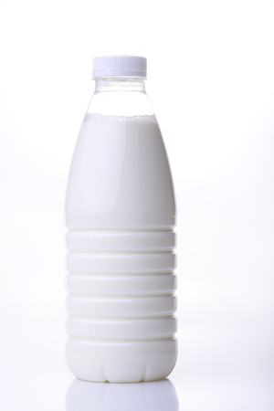 dairying: Big plastic bottle of fresh useful home milk standing on white background, vertical photo Stock Photo
