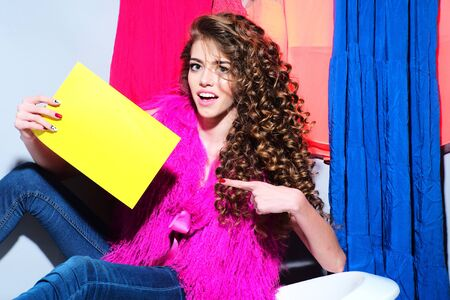 pink fur: Fashionable sexual young woman with curly hair in pink fur vest and blue jeans holding yellow cardboard sitting on white bathtub amid colorful clothes pink orange red blue colors on grey wall background copy space, horizontal picture