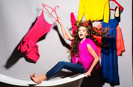 pink fur: Cool emotional young woman with curly hair in pink fur vest and blue jeans sitting in white bathtub amid colorful clothes pink orange red blue colors on grey wall background, horizontal picture Stock Photo