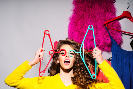 teenage girl dress: Crazy young girl with curly hair in yellow sweater holding hangers standing amid colorful clothes pink red blue colors on grey wall background, horizontal picture