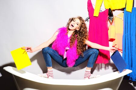 pink fur: Fashionable funny young woman with curly hair in pink fur vest and blue jeans holding yellow cardboard sitting on white bathtub amid colorful clothes pink orange red blue colors on grey wall background copy space, horizontal picture