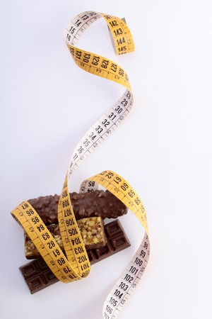 dietology: Tasty chocolate bars and peanut brittle with a measuring tape as a symbol of diet on white background, vertical photo
