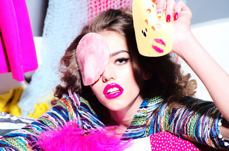 the lipstick: Portrait of beautiful blazing girl holding slice of cheese with pink lipstick kiss and bacon on face looking forward amid colorful clothes on grey wall background, horizontal picture Stock Photo
