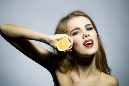 Cute blonde girl portrait with bright make up looking forward holding half of fresh juicy orange standing on gray background copyspace, horizontal picture photo