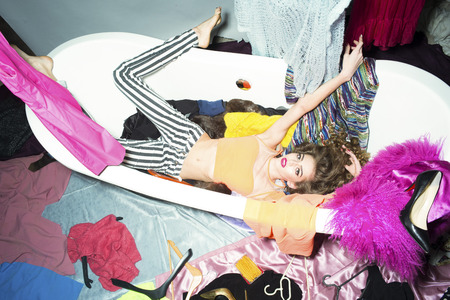 lying in bathtub: Showy effective young woman with curly hair lying in white bathtub amid colorful clothes pink orange red blue colors on grey wall background, horizontal picture