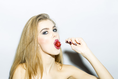 impassioned: Impassioned blonde young woman portrait with bright make up looking forward holding and licking round red sugar candy standing on light gray background copyspace, horizontal picture Stock Photo