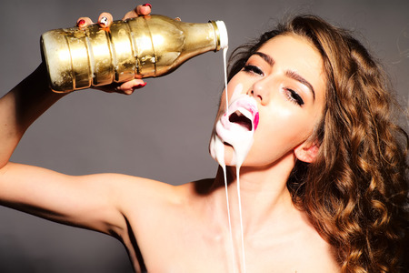 pours: Impassioned attractive young woman with curly hair holding gold bottle pours white yogurt on her face with open mouth looking forward standing on grey background, horizontal picture Stock Photo