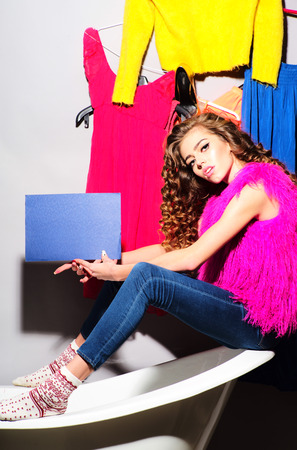 pink fur: Fashionable sexy young woman with curly hair in pink fur vest and blue jeans holding blue cardboard sitting on white bathtub amid colorful clothes pink orange red blue colors on grey wall background copy space, vertical picture