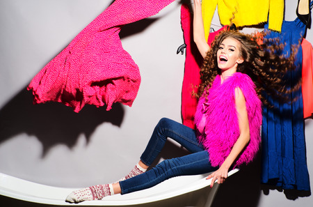 Crazy emotional young woman with curly hair in pink fur vest and blue jeans sitting in white bathtub amid colorful clothes pink orange red blue colors on grey wall background, horizontal picture