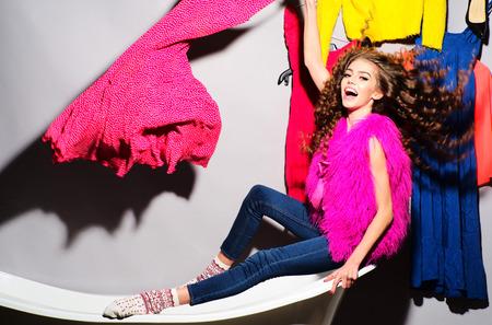 hair curly: Mujer joven loca emocional con el pelo rizado en chaleco de piel rosada y tejanos que se sientan en la bañera blanca en medio de la ropa de colores naranja azul colores rojo rosa sobre fondo gris de la pared, cuadro horizontal