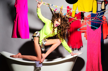 hitched: Beautiful crazy young girl with curly hair in skirt and blouse standing in white bathtub with hair hitched clothespins amid colorful clothes pink orange red blue colors on grey wall background, horizontal hair hitched clothespinspicture Stock Photo