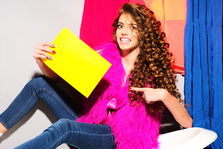 pink fur: Fashionable smiling young woman with curly hair in pink fur vest and blue jeans holding yellow cardboard sitting on white bathtub amid colorful clothes pink orange red blue colors on grey wall background copy space, horizontal picture
