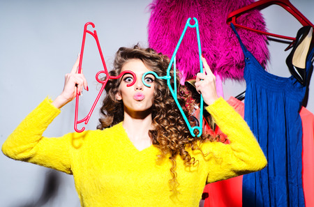 girl in red dress: Sensual young girl with curly hair in yellow sweater holding hangers standing amid colorful clothes pink red blue colors on grey wall background, horizontal picture Stock Photo