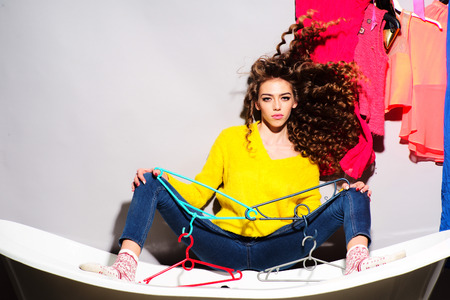 Attractive beautiful young woman with curly hair in yellow sweater and blue jeans holding hangers sitting on white bathtub amid colorful clothes pink orange red blue colors on grey wall background, horizontal picture