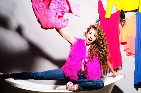 pink fur: Funny emotional young girl with curly hair in pink fur vest and blue jeans sitting in white bathtub amid colorful clothes pink orange red blue colors on grey wall background, horizontal picture Stock Photo