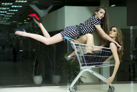 svelte: Horizontal photo with two young attractive sensual cheerful girls with bright makeup and beautiful svelte legs where one in short dress with white polka dots and black red shoes high heels with flowing straight hair jumped on shopping cart with a girl sit Stock Photo