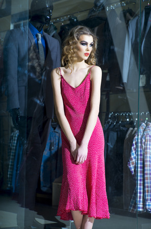 shopaholism: Alluring young girl with bright make up curly hair and red dress standing near shopping window indoor, vertical picture Stock Photo