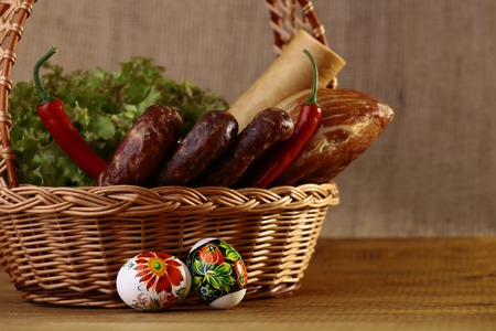 heathy diet: Meat home made tasty sausages lattuce bread rolls red pepper and easter eggs in basket, horizontal picture Stock Photo