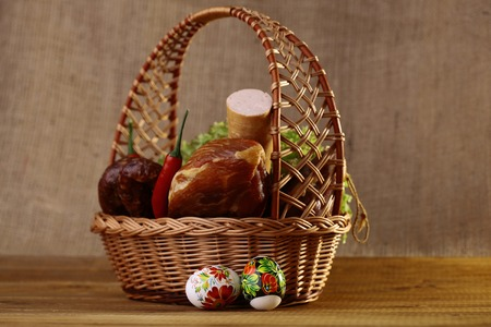 Meat home made delicious sausages lattuce bread rolls red pepper and easter eggs in basket, horizontal picture