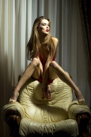 mujer desnuda sentada: Chica joven sexual siiting en el sill�n de cuero blanco sobre fondo rico interior de una casa, imagen vertical