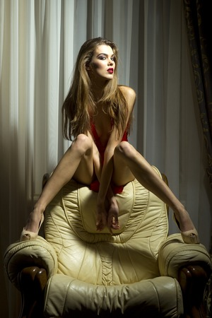 nude pose: Sexual young girl siiting in white leather armchair on rich home interior background, vertical picture