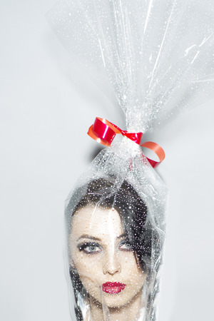 creatively: Head of pretty young brunette woman with bright makeup in cellophane present packing with red bow on white background, vertical picture Stock Photo