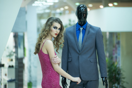 male mannequin: Alluring young girl with bright makeup and curly hair standing with male mannequin in formal clothes on shopping background, horizontal picture
