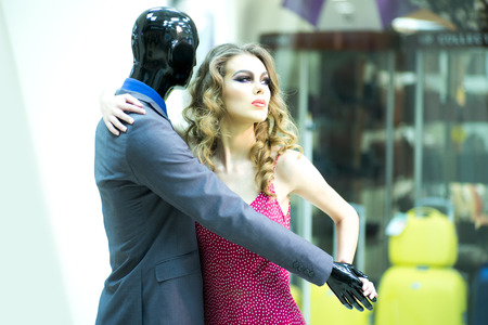 male mannequin: Tempting secretive young girl with bright makeup and curly hair dancing with male mannequin in formal clothes on shopping background, horizontal picture Stock Photo