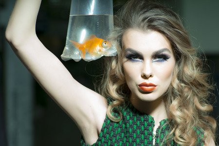 skintone: Sexy young girl with bright makeup and blonde curly hair holding cellophane package aquarium with goldfish, horizontal photo Stock Photo