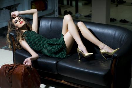Sensuele slanke jonge blonde vrouw in een groene jurk en gouden schoenen met bruine zak liggend op zwart lederen bank, horizontaal beeld Stockfoto