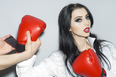 activity adult: Sexual strong brunette girl with bright makeup in white blouse and red boxing gloves standing on light grey backdrop, horizontal picture