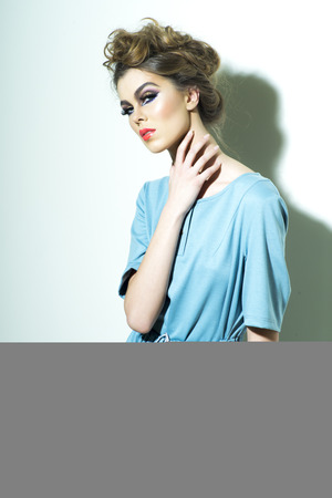 chignon: Pretty fashionable woman with bright makeup and chignon in light blue dress standing on white background, vertical picture Stock Photo