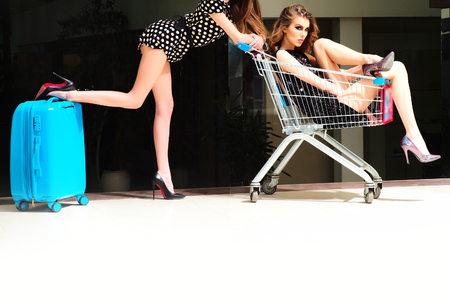 Two cute pretty girls in dresses with shopping trolley and blue bag indoor on shop background, horizontal picture