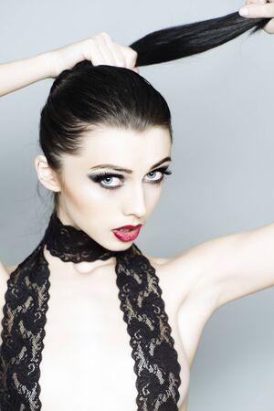 nude woman: Chica morena joven atractiva con el pelo brillante del maquillaje en la cola y encaje negro en el cuello con ganas de pie sobre fondo gris, imagen vertical