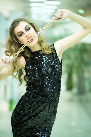 black sex: Alluring young blonde woman in back dress in sequins with gold chin standing on store background, vertical picture Stock Photo