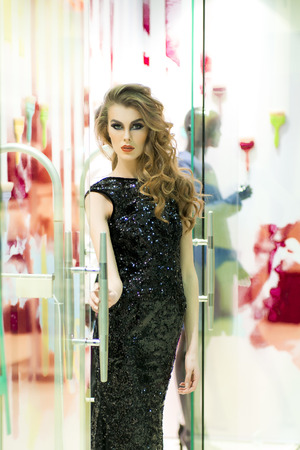 sequins: Sexual young blonde woman in back dress in sequins standing on store background, vertical picture