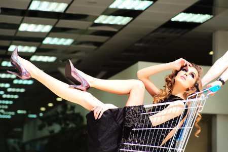 One young pretty fashion girl in black dress sitting in shopping trolley indoor on store backdrop, horizontal picture